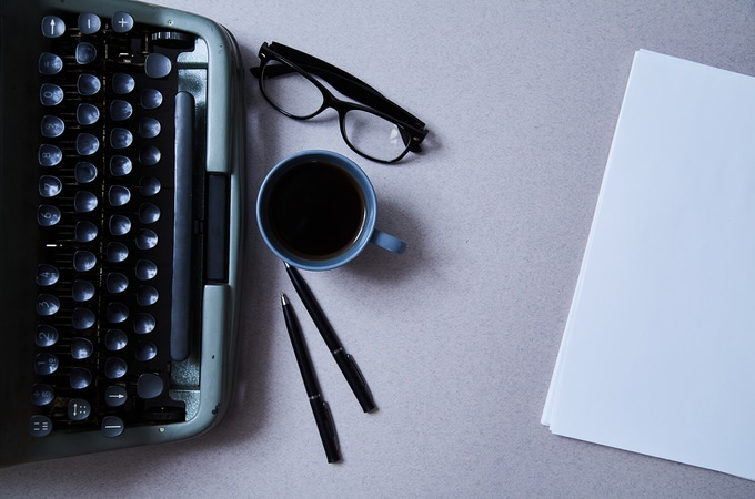 Table with type writer, glasses and cup of coffee