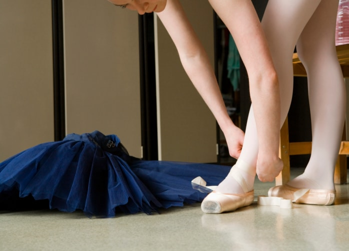 Ballerina putting on Ballet shoes