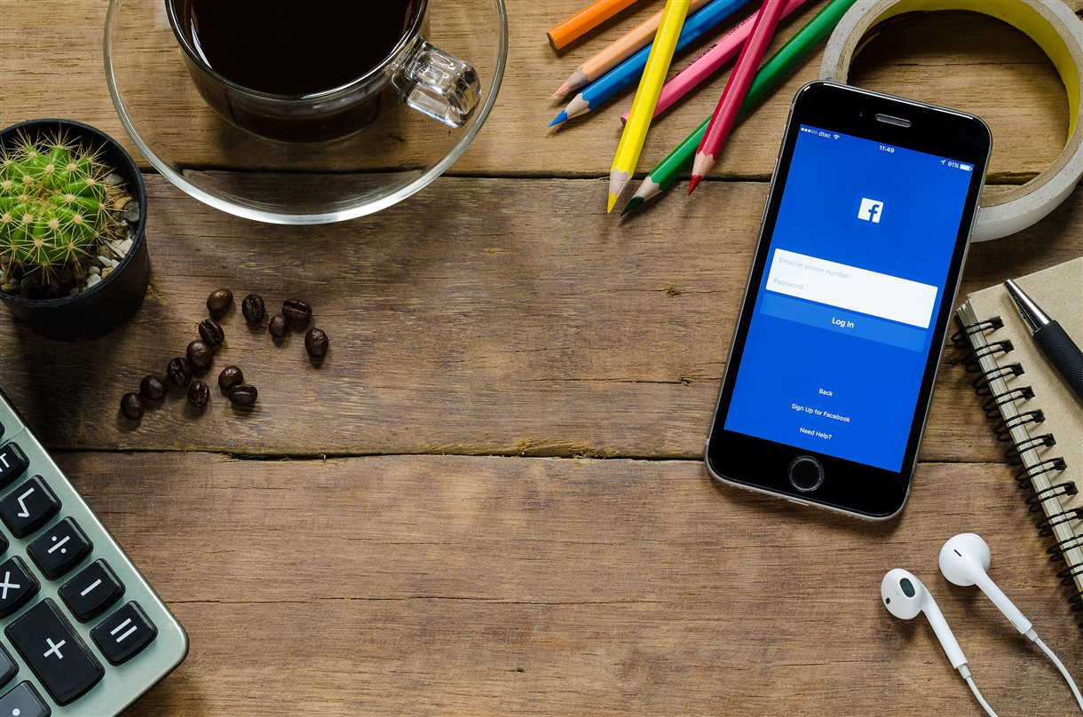 Table with mobile phone showing Facebook login screen