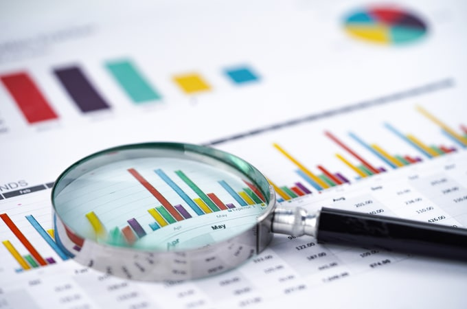 Magnifying Glass On Charts Graphs Spreadsheet Paper.