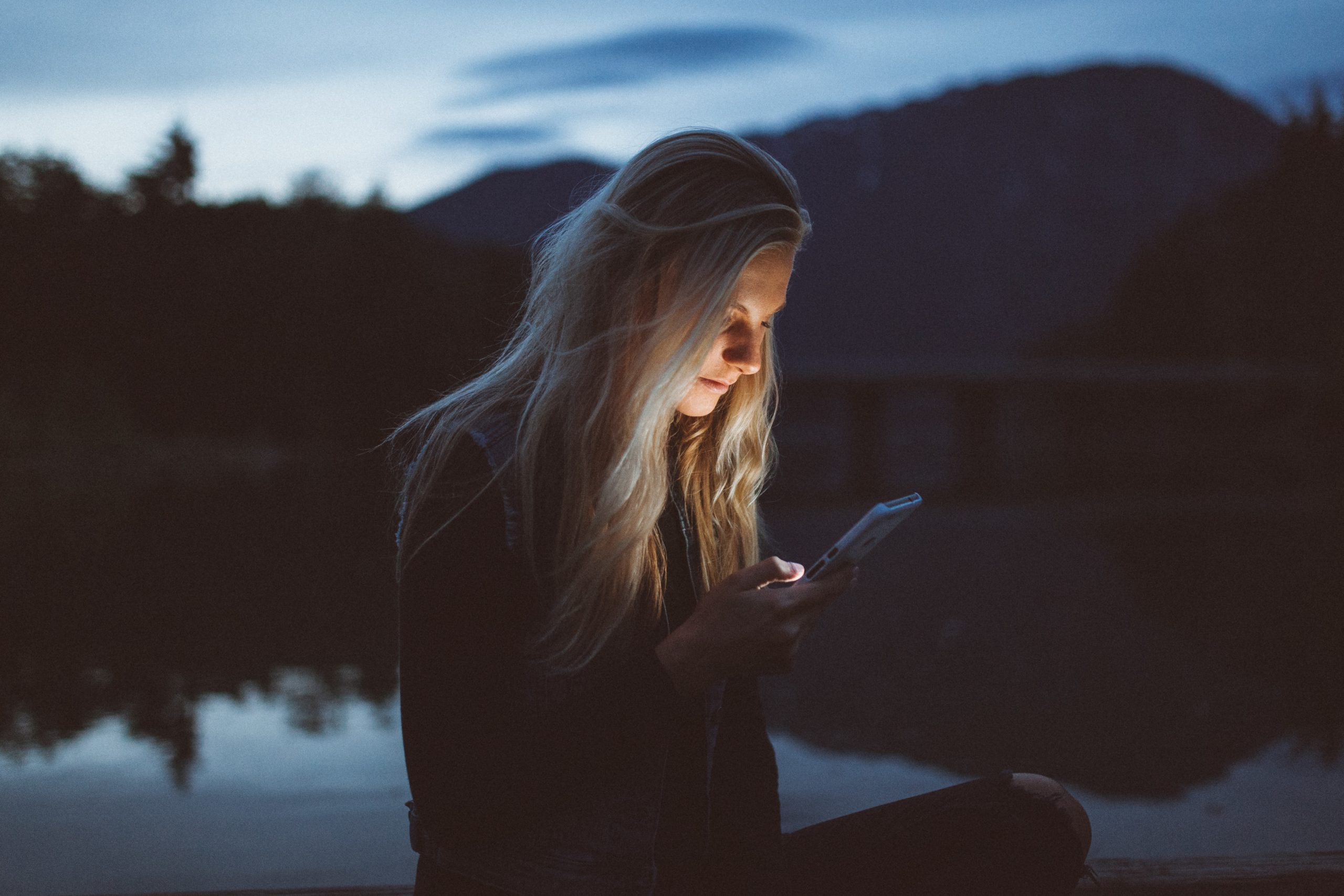 lady using phone at dusk