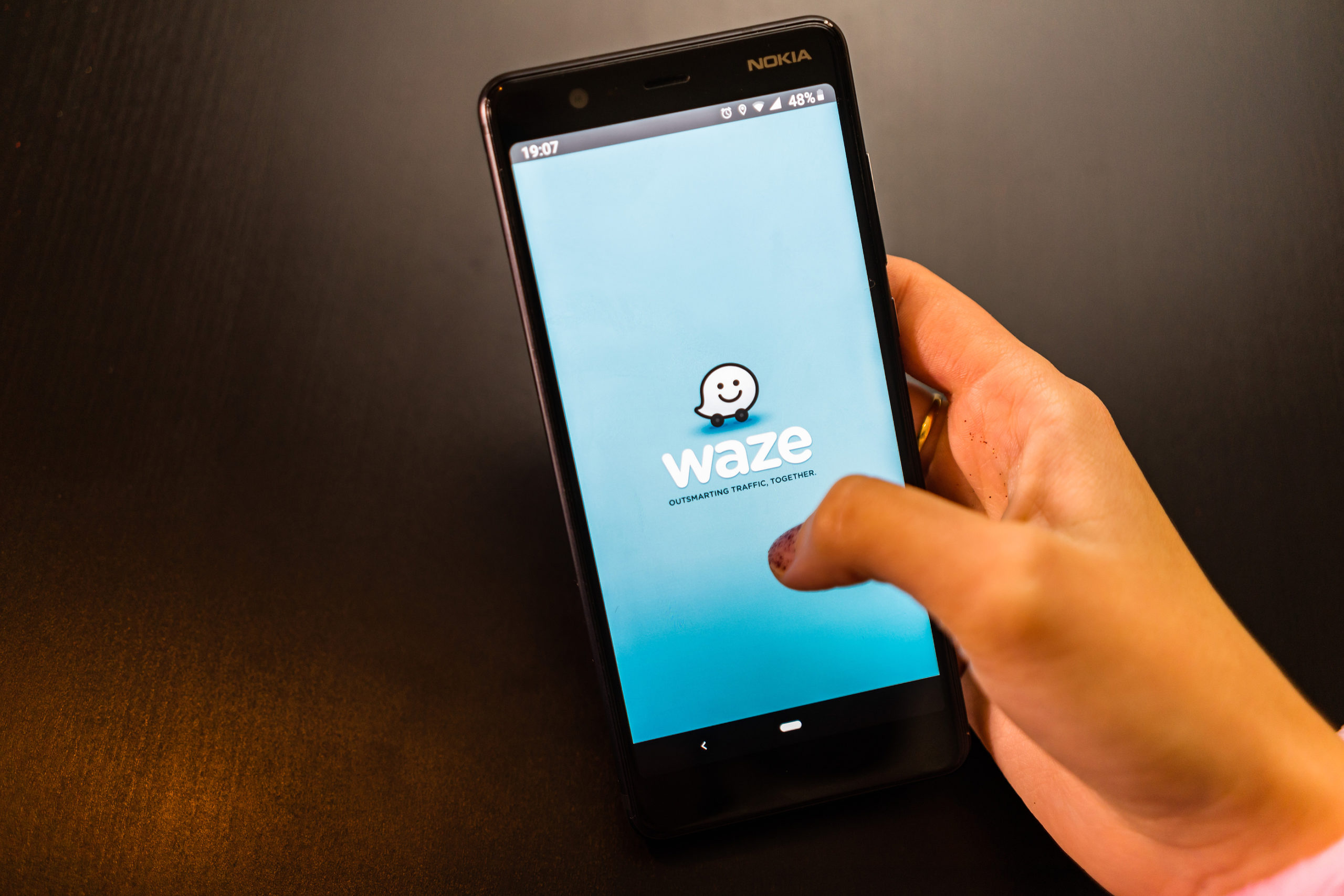 Hand holding a phone with Waze