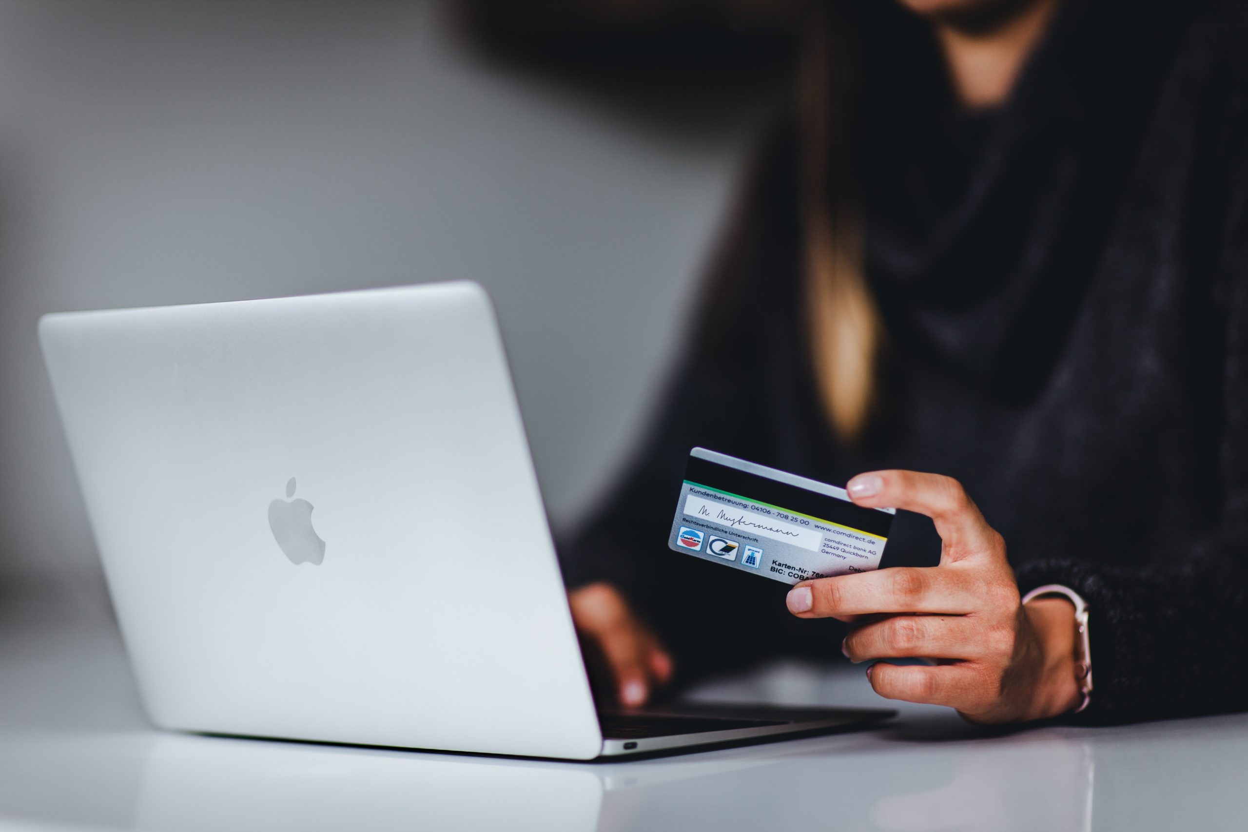 Person in front of laptop holding a credit card